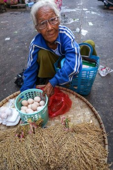 Street seller in a Yangon market with eggs