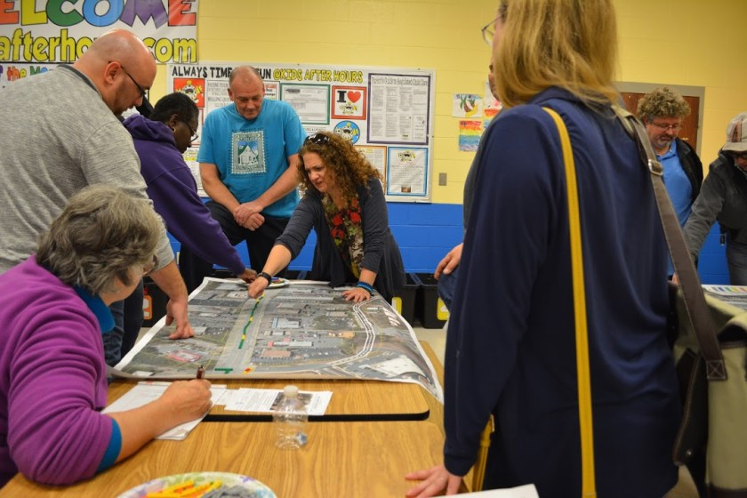 Photo of charrette participants placing LEGO blocks on a large aerial image of Burtonsville