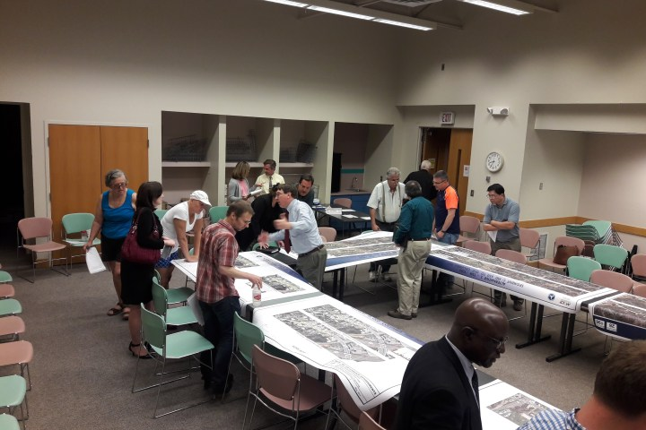 Photo of people looking at highway project maps.
