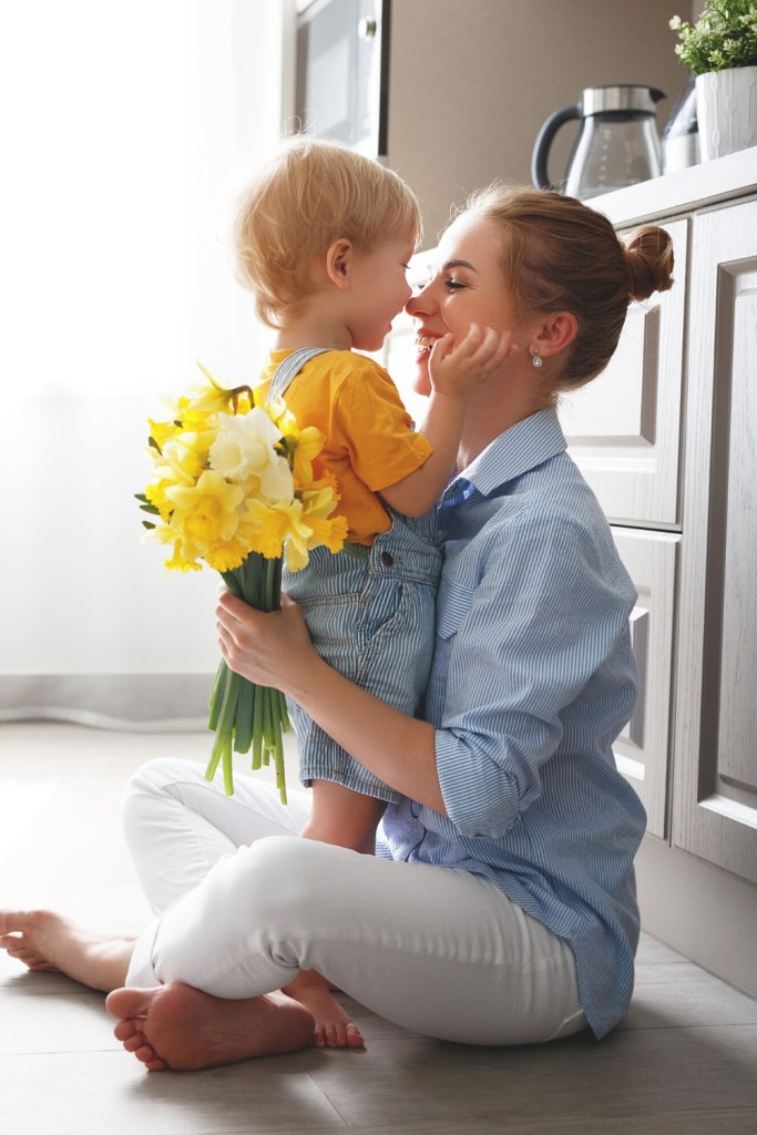 Toddler boy hugging mom who has flowers in her hand