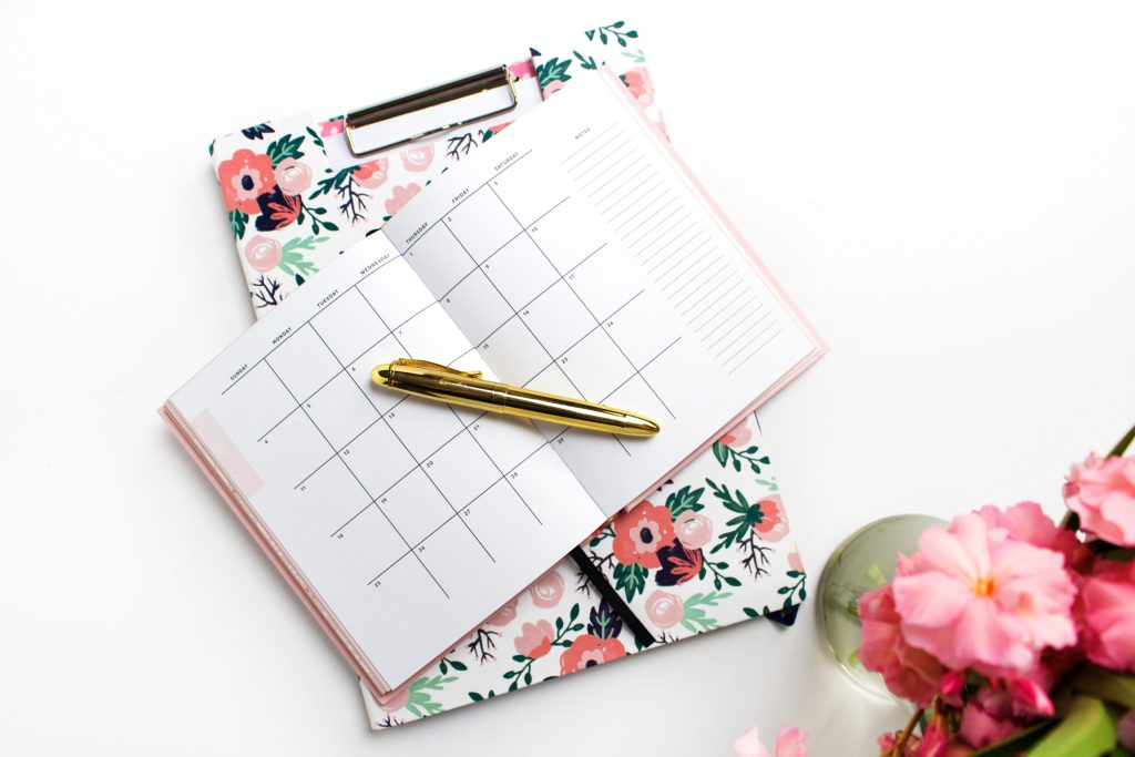 floral clipboard with calendar and pen on top