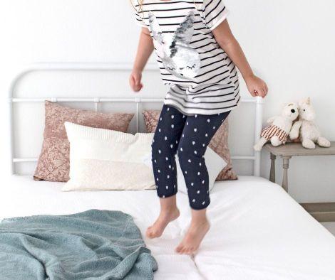 little girl jumping on white bed