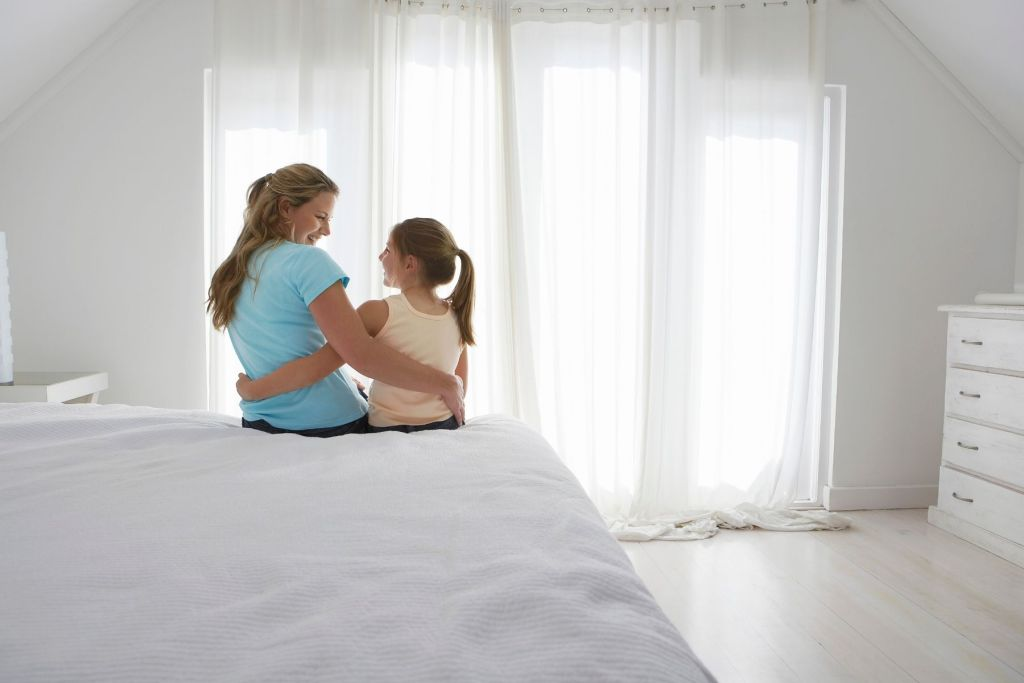 Mother and daughter sitting on a bed with their arms around each other.