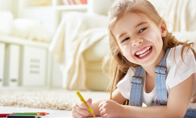 Young girl drawing with colored pencils, smiling