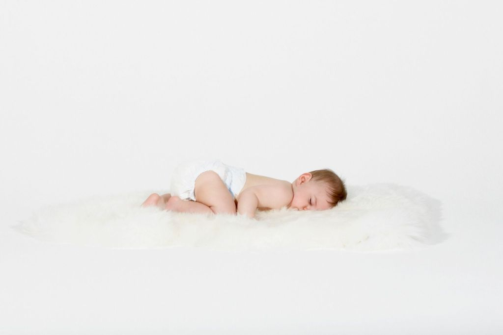 Baby wearing diaper and sleeping on white fur rug