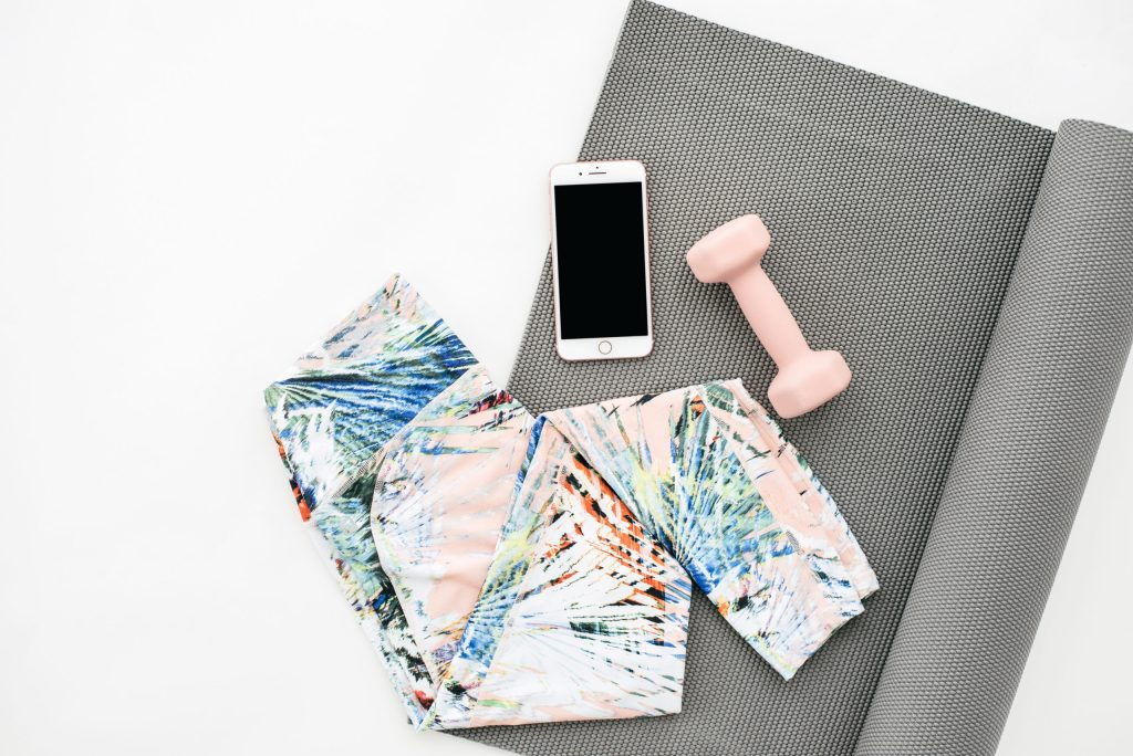 grey yoga mat with yoga pants, pink weight and iPhone on top