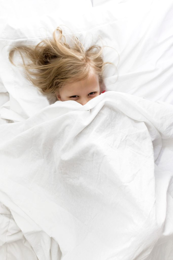 Young girl peeking out from under the covers of a white bed.