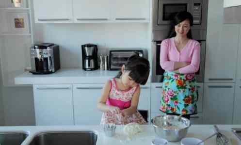 mom of a big family watching daughter cook