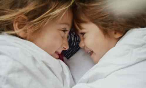two sisters from a big family smiling at each other