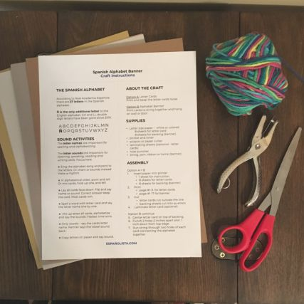instructions colored paper yarn hole puncher and scissors on wood table
