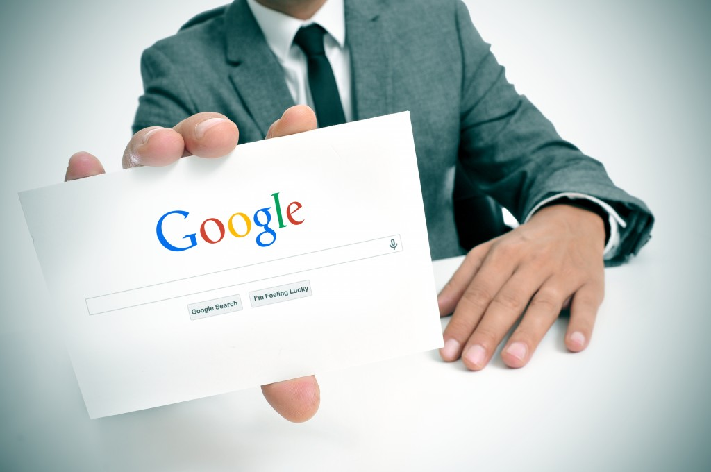 BARCELONA, SPAIN - SEPTEMBER 26, 2013: Businessman holding a signboard with the Google Web Search homepage