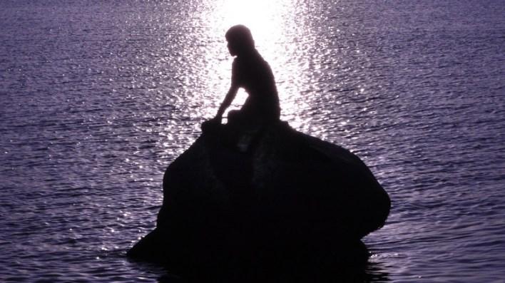 silhouette of mermaid on rock