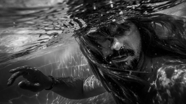 Merman with hair flowing in water