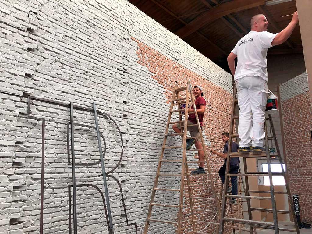 Pintores de Grupo Aranda pintando la pared de ladrillo ficticio para Al Rojo Vivo