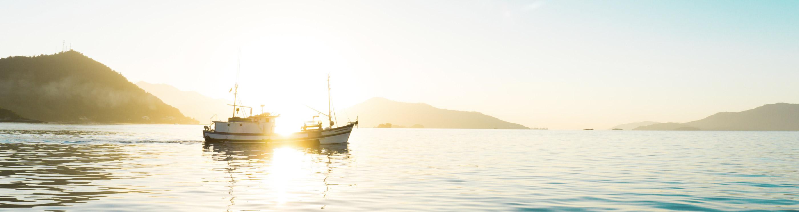 Paisaje de dos barcos en el mar con puesta de sol y montañas