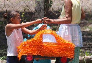 Señora de avanzada edad dando una piñata a una niña