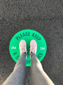 """Photograph of someone's feet, standing on a green circle which says """"Please Keep a Safe Distance"""""""