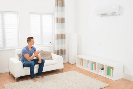 man using remote to operate air conditioner