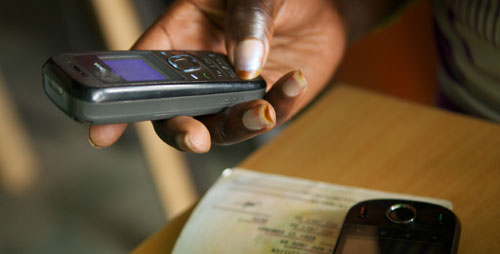 A Safaricom agent registers the user for the mPesa system