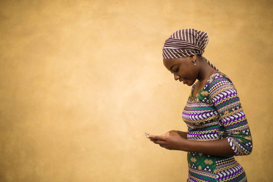Side view of a young African girl dressed in traditional clothing and a headscarf standing against a plain brown yellow warm background communicating on her mobile phone in Dar es Salaam East Africa