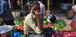 onion-selling-boy-holding-mobile-phone-resized