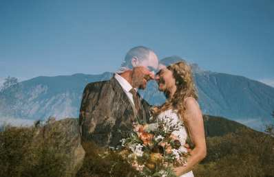 A bride and groom near Mt Pilchuck in North Bend at Meadowbrook Farm double exposure wedding photo with bouquet