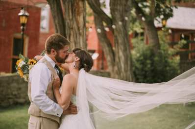 Wedding Couple Kissing in Reeder's Alley in Helena MT with her veil blowing in the wind. She has a bouquet of succulents and sunflowers