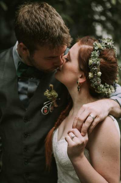 Bride and groom kissing showing off rings in Seattle at Bell Harbor bride has a hops flower crown and a lace embroidered dress and red hair