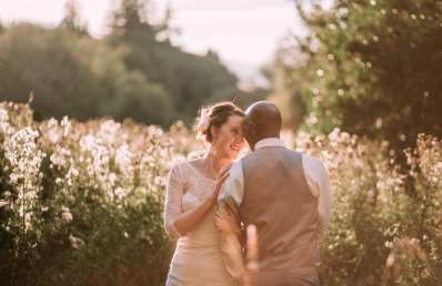 Couple in a Thistle Field. interracial Wedding, Bride and Groom during a Summer Sunset.