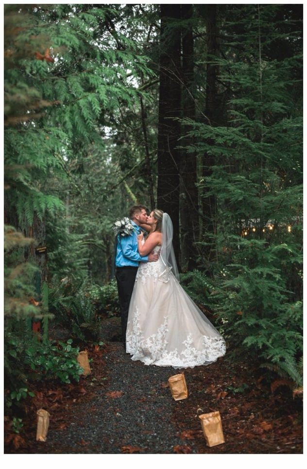 Winter Wedding Bride and Groom at the Lookout Lodge in Snohomish with Lumineries on a path with trees