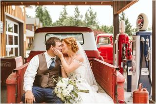 mt vernon wedding bride and groom in a red antique truck bed kissing with white flowers seattle snohomish skagit wedding photography
