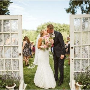 barn at holly farm bothell ceremony outdoors with barn doors in the summer with blush pink bouquet bride and groom kissing