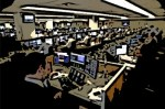 Many traders sitting in front of trading desks in institutional trading firm.
