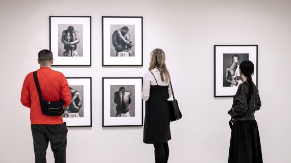 Man in a red shirt, a woman in a black jumper over a white blouse, and a woman in black stand in front of five black and white photos by Robert Mapplethorpe