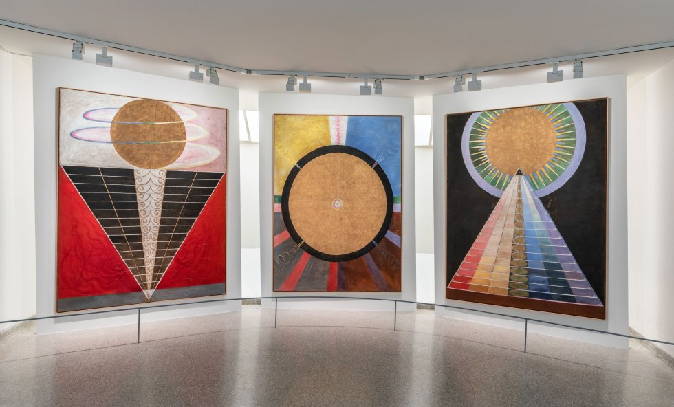 Three large, colorful painting by Hilma af Klint featuring large, gold circles and rays of red, blue, and yellow