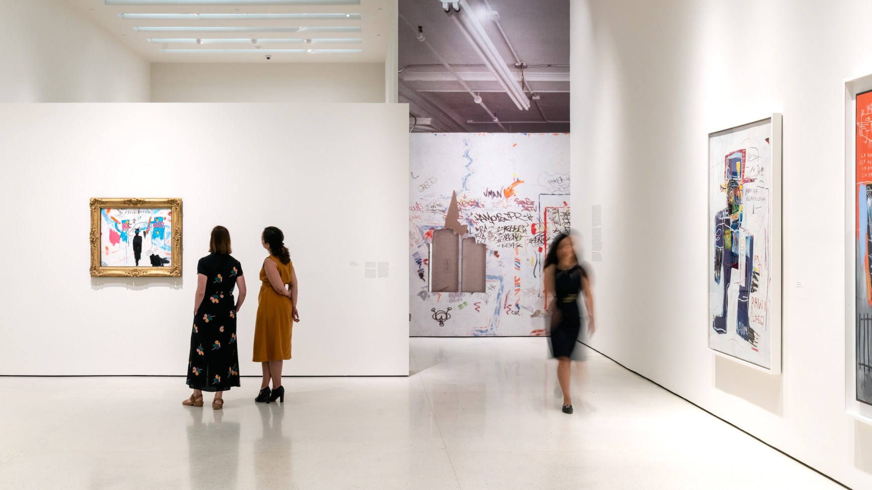 Two women look at Basquiat's painting The Death of Michael Stewart, while another woman walks by in the gallery, which has supporting works on the walls