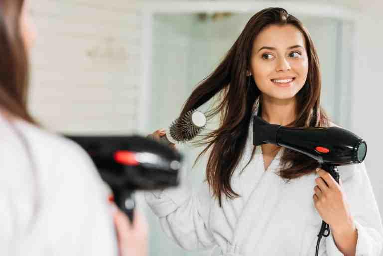 Imagem de mulher secando o cabelo.