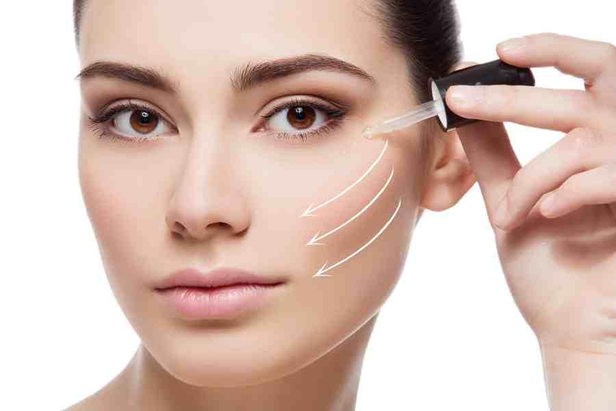 Imagem mostra uma mulher aplicando sérum no rosto