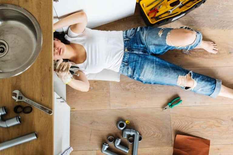 Mulher fazendo conserto em pia.