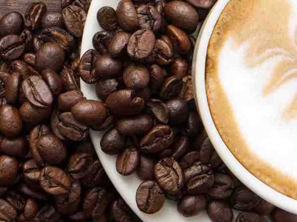 Xícara de café e vários grãos de café espalhados