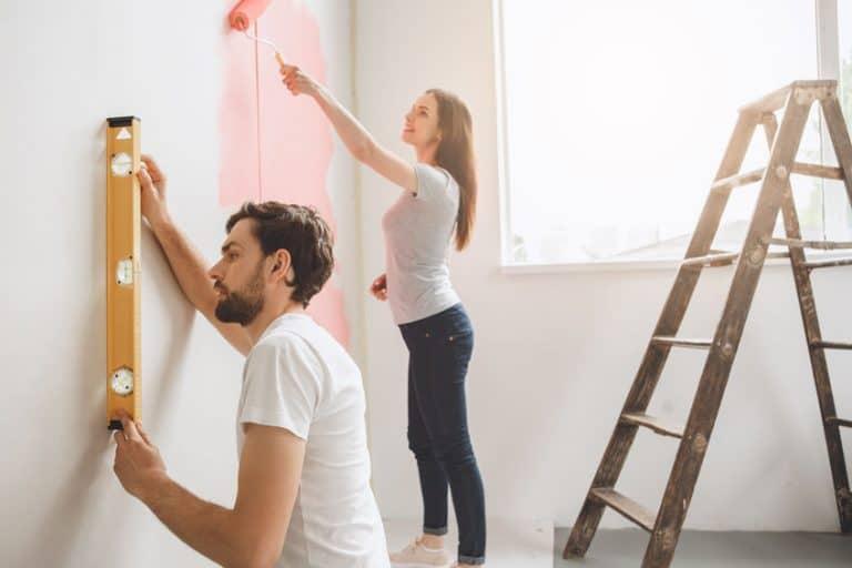 Casal pintando parede.