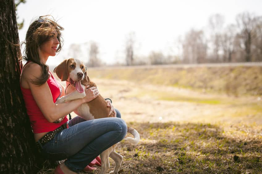Image of woman in park with dog on her lap.