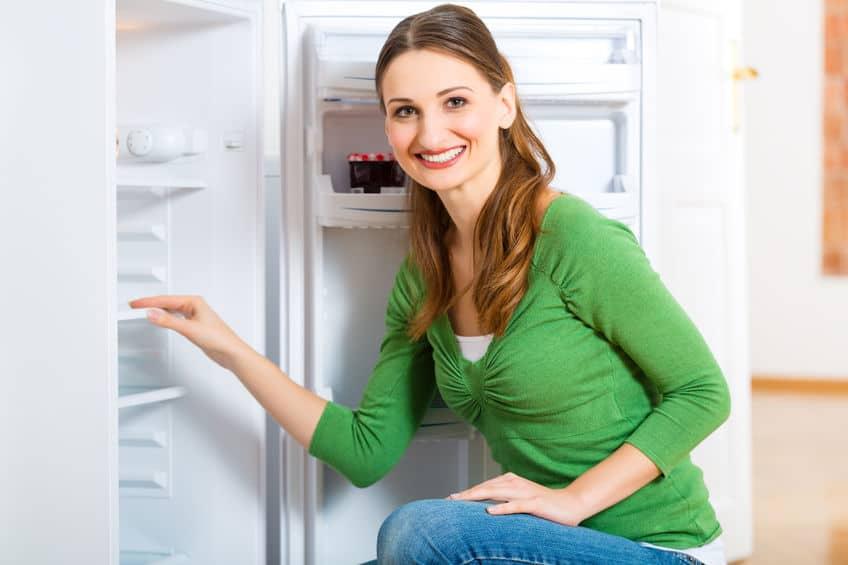 Imagem de mulher sorrindo em frente a freezer.