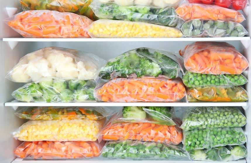 Imagem de legumes em sacos congelados dentro de freezer.