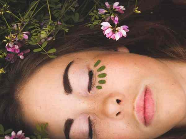 Mulher com maquiagem deitada de olho fechado.