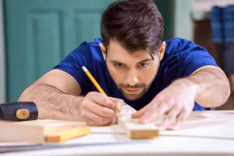 Homem fazendo medição na madeira com esquadro