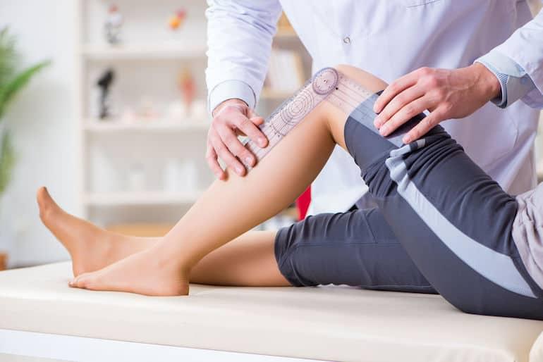 Imagem de médico fazendo medição em joelho de paciente.