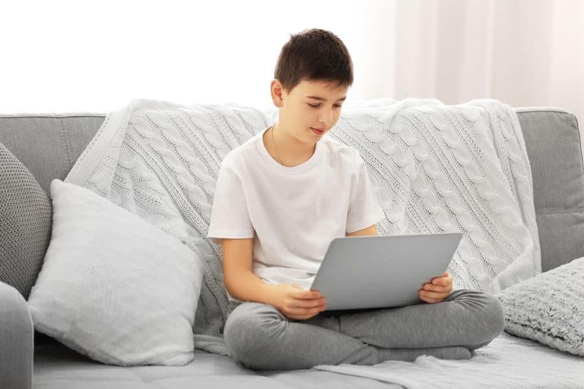 Imagem de menino em sofá.