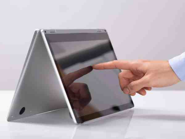 Close-up Of Businessman Touching His Finger On Hybrid Laptop Screen On White Desk