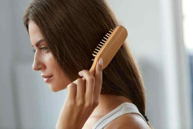 Mulher escovando cabelo com escova de madeira.